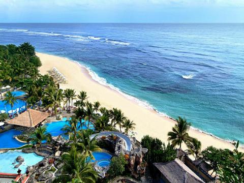 Вид на бассейны отеля и пляж на курорте Санур