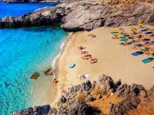Пляж с пологим спуском и светлым песком отлично подойдет для отдыха с ребенком в Греции.